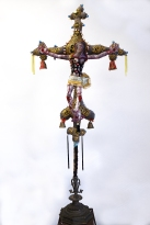 The Anchorite's Crucifix 2019 Mixed media: acrylic painted canvas, recycled fabric, beads, bells, embroidery floss, black-pipe interior structure, poly-fil, discarded furniture and metal work Crucifix: 60 by 32 by 10 inches; total installation varies upon situation.